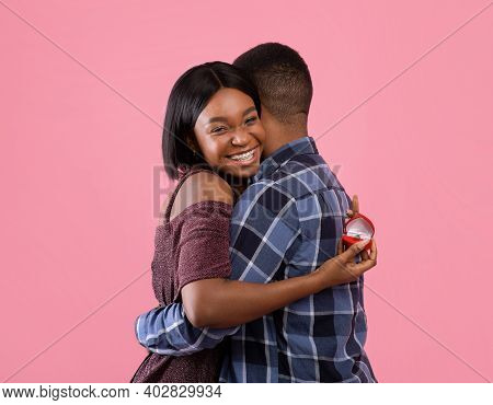 Happy Black Woman Hugging Her Fiance And Holding Engagement Ring On Pink Studio Background. Passiona