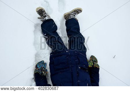 School Boy In Winter Clothes Playing In The Snow. Sometimes He Lies On The Ground On His Back And Re