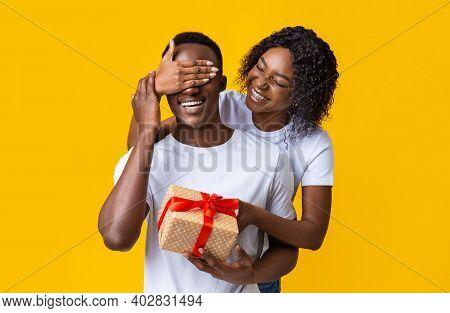 Happy Young Black Lady Giving Present To Her Boyfriend. Covering His Eyes And Holding Festive Giftbo