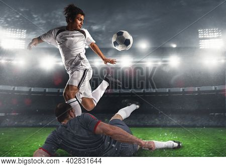 Close Up Of A Football Action Scene With Competing Soccer Players At The Stadium During A Night Matc