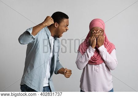 Domestic Violence, Abuse Concept. Young African-american Violent Man Threatening His Crying Girlfrie