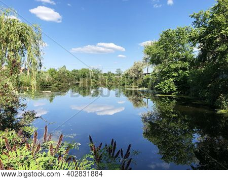 Peacefull Scene Of Summer Lake With Reflection Of White Clouds In It, Green Trees Are On Sides Of La