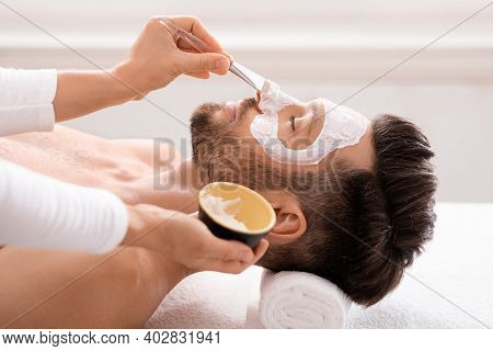 Side View Of Bearded Caucasian Man Getting Face Treatment At Modern Spa Salon. Female Attendant Appl