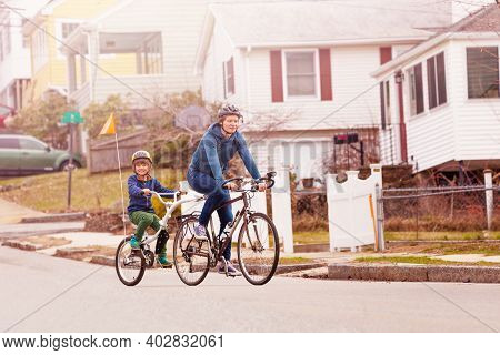 Family Bike Portrait With Little Happy Boy Ride On A Tow Tandem Bicycle Attached To Father On Urban