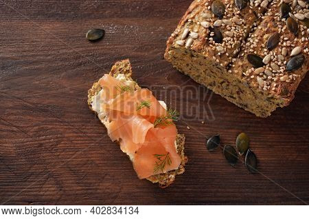 Healthy Low Carb Protein Bread From Lupine Flour And Pumpkin Seeds With Salmon And Herb Garnish On A
