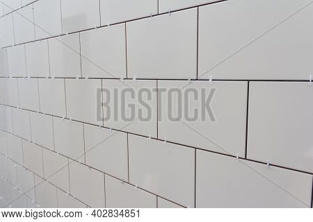 Laying Ceramic Tiles On The Wall. White Ceramic Tiles. Renovation Work. Ceramic White Tiles On Wall,