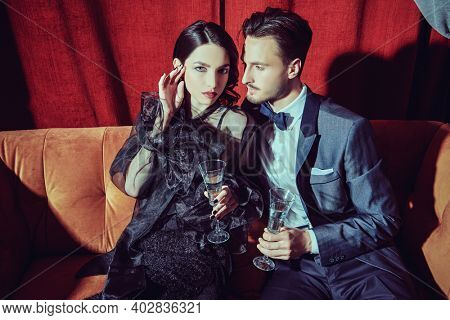 Beautiful elegant couple in fashionable evening clothes drinking champagne in a luxury apartment. Glamorous lifestyle. Fashion shot.