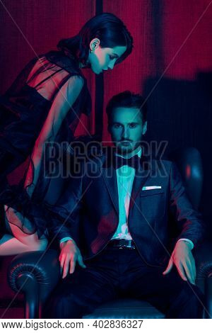 Glamorous lifestyle. Beautiful elegant couple in fashionable evening clothes posing in a luxury apartment. Fashion shot.