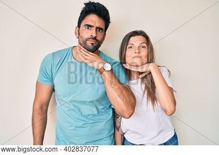 Beautiful young couple of boyfriend and girlfriend together cutting throat with hand as knife, threaten aggression with furious violence