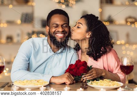 Celebrating Special Day. Beautiful Black Girlfriend Kissing Her Smiling Boyfriend In Cheek, Holding