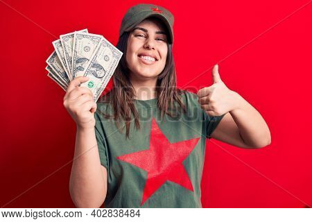 Woman wearing t-shirt with red star communist symbol holding bunch of dollars banknotes smiling happy and positive, thumb up doing excellent and approval sign