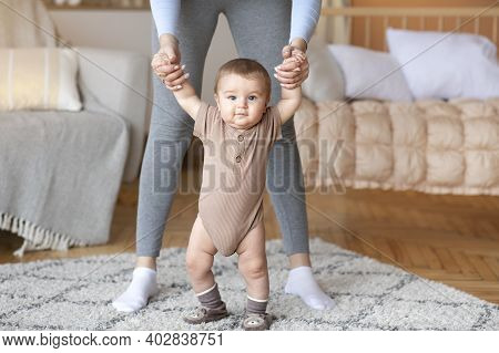 Cute Little Baby Boy Or Girl Taking First Steps With Mother Help, Home Interior, Close Up. Adorable
