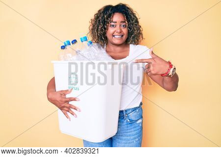 Young african american plus size woman holding recycling wastebasket with plastic bottles smiling happy pointing with hand and finger