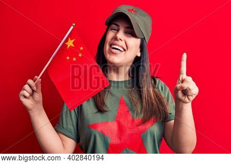 Beautiful patriotic woman wearing t-shirt with red star communist symbol holding china flag smiling with an idea or question pointing finger with happy face, number one