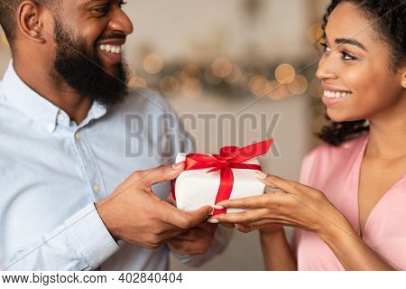 Closeup Of Happy Lovers Exchanging Gifts On Holiday, Anniversary, St Valentines Day Or Birthday. Hap