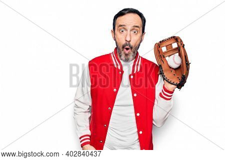 Middle age handsome sporty man wearing jacket playing baseball using glove and ball scared and amazed with open mouth for surprise, disbelief face