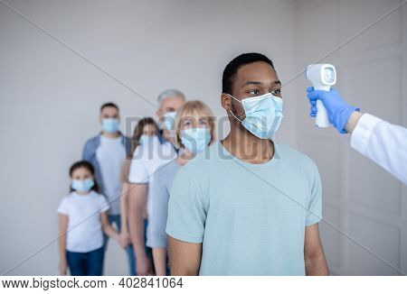 Coronavirus Immunization Medical Campaign Concept. Black Man In Face Mask Standing In Line At Clinic