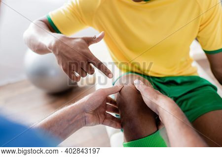Cropped View Of Injured African American Sportsman Pointing With Finger At Knee Near Chiropractor
