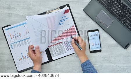 Trader Man Counting Analyzing Financial Report In Clipboard. Finance And Profit Concept. Close Up
