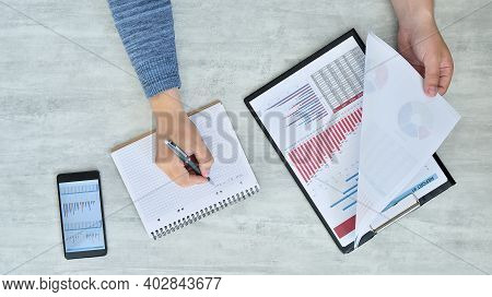 Top View Of Trader Man Checking Profits And Drawing Data In Note Pad. Paperwork And Financial Succes