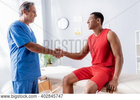 Happy African American Man In Sportswear Shaking Hands With Chiropractor In Clinic