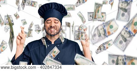 Young hispanic man wearing cooker uniform gesturing finger crossed smiling with hope and eyes closed. luck and superstitious concept.