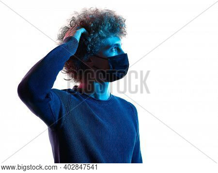 one caucasian young man portrait wearing a mask thinking looking up in studio shadow isolated white background