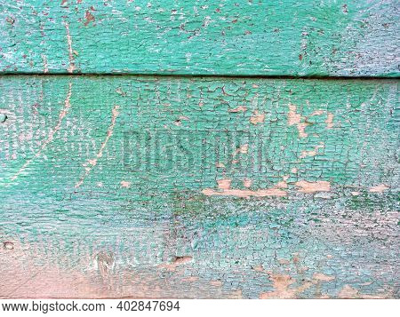 Close-up Old Green Cracked Paint On Wood. The Texture Of The Old Emerald Paint With Cracks. Dried In
