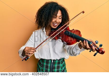 Beautiful african american woman with afro hair playing classical violin smiling and laughing hard out loud because funny crazy joke.