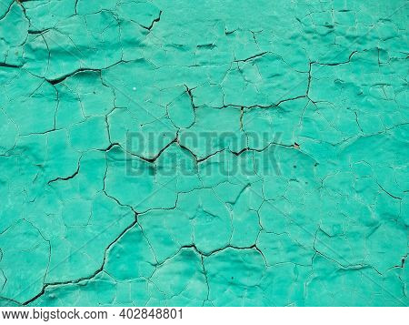 Close-up Old Green Cracked Paint. The Texture Of The Old Emerald Paint With Cracks. Dried In The Sun