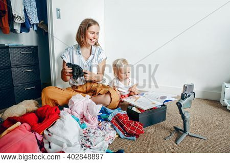 Young Mother Blogger Doing Video Live Stream For Social Media While Sorting Clothes At Home. Video C