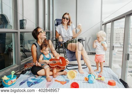 Young Mothers Spending Time Together With Children Babies On Balcony At Home. Staycation During Coro