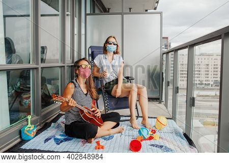 Young Lesbian Lgbtq Women Family Spending Time Together On Balcony At Home. Staycation During Corona