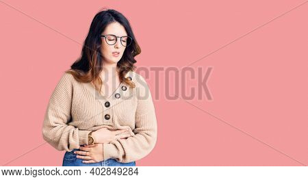 Beautiful young brunette woman wearing casual clothes and glasses with hand on stomach because indigestion, painful illness feeling unwell. ache concept.
