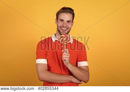 Sweet That Speaks. Sweet Tooth Yellow Background. Happy Man Hold Candy On Stick. Sweet Snack. Sweet