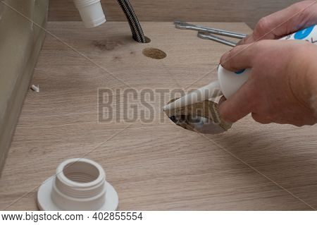 Installing The Sink On A Wooden Countertop. The Saw Cut With Acrylic Sealant. Plumber Work.