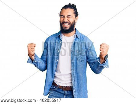 Young arab man wearing casual denim shirt very happy and excited doing winner gesture with arms raised, smiling and screaming for success. celebration concept.