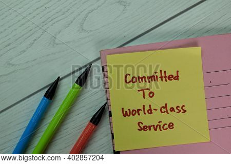 Committed To World-class Service Write On Sticky Notes Isolated On Wooden Table.