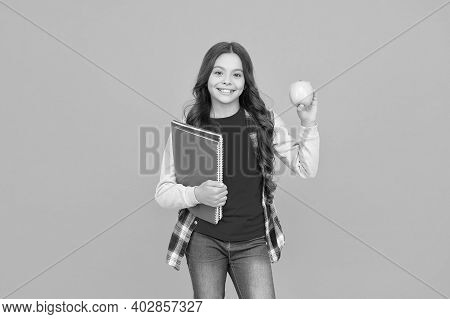 Feed Your Brain With Knowledge. Happy Kid Hold Apple And Books Orange Background. Symbol Of Knowledg