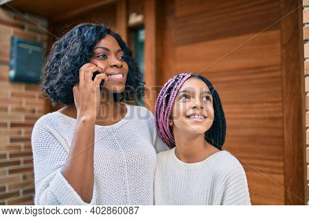 African american mother and daugther hugging and talking on the smartphone at the city.