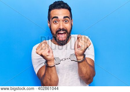 Young hispanic man wearing prisoner handcuffs screaming proud, celebrating victory and success very excited with raised arms