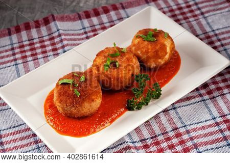 Delicious Hot Italian Arancini - Rice Balls Stuffed With Cheese In Tomato Sauce, In A Plate On An Ol