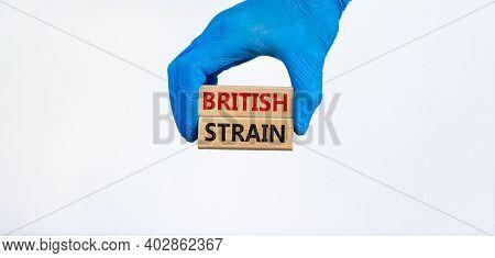 Covid-19 British Strain Symbol. Hand In Blue Glove Holds Wooden Blocks, Words 'british Strain'. Beau