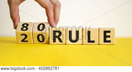 80 On 20 Rule Symbol. Pareto Principle. Male Hand Flips Wooden Cubes With Words '80 On 20 Rule'. Bea