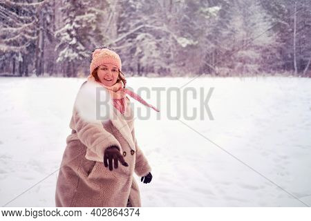 Woman Throws A Snowball At Camera In A Winter Forest. A Woman Plays Snowballs Among The Snow Covered