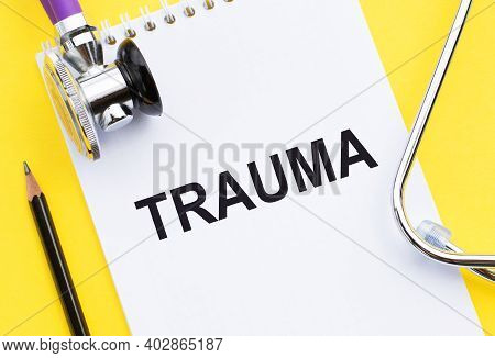 On A Yellow Background, A Notebook With The Word Trauma, Next To A Pencil And A Stethoscope. Medical