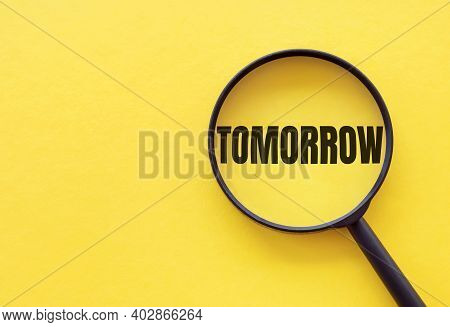 The Word Tomorrow Is Written On A Magnifying Glass On A Yellow Background.