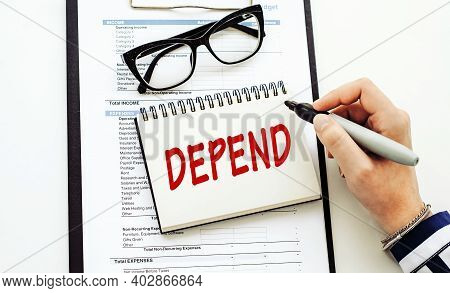 Depend Text Written By Business Woman In Her Diary On Office Desk.