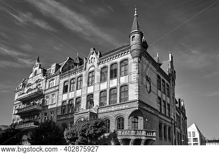 Neo-gothic Facade Of A Historic Red Brick Tenement House In Poznan, Monochrome
