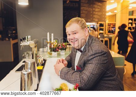 Guy Spend Leisure In Bar, Defocused Background. Man With Strict Face Sit In Bar Or Pub Near Bar Coun